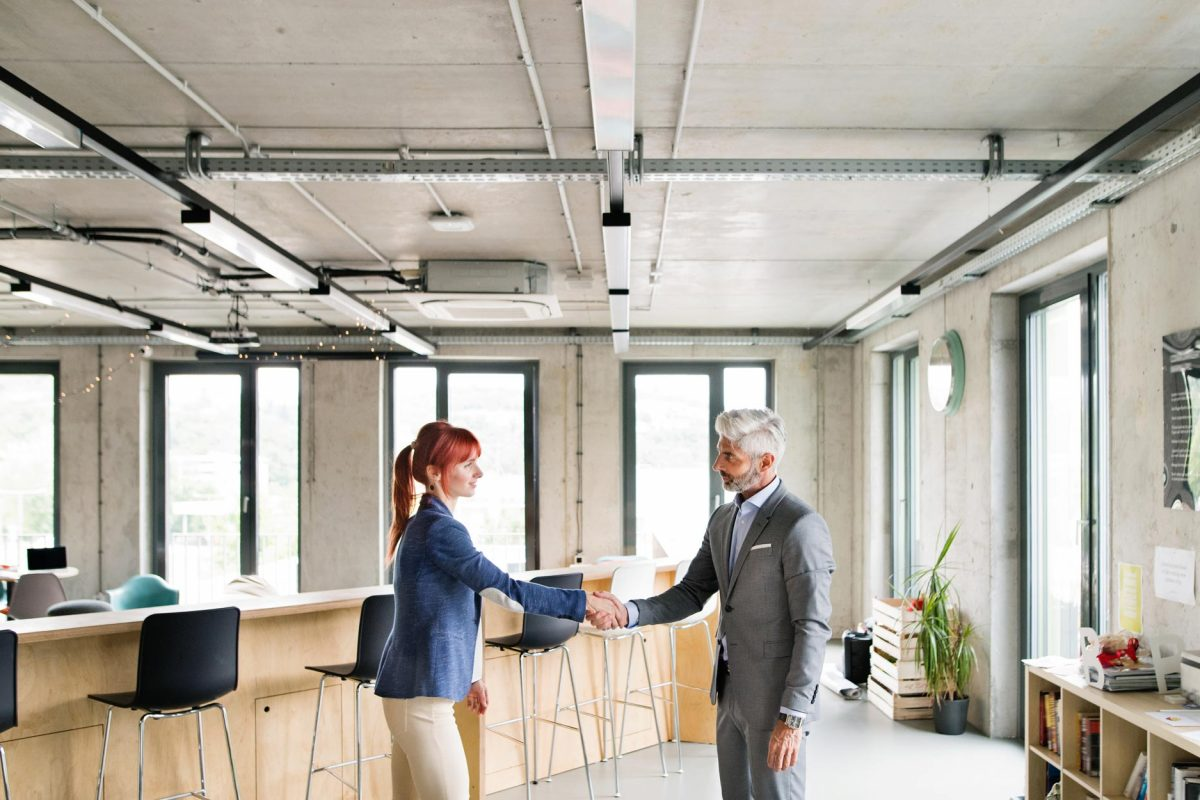 two-business-people-in-the-office-shaking-hands-PWRS4YC.jpg